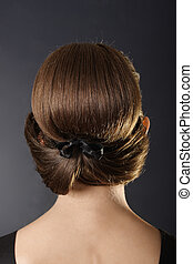 Classic hairstyle - Woman standing back with classic bun...