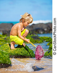 Young boy having fun on tropical beach, playing with fishing...
