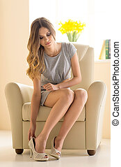 Beauty at home. Beautiful young woman in dress wearing shoes