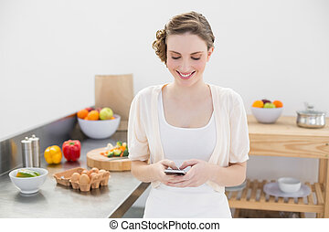 Cheerful young woman messaging with her smartphone standing...