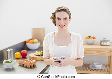 Peaceful lovely woman holding her smartphone standing in the kitchen smiling at camera