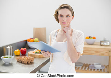 Thinking gorgeous woman standing in kitchen while holding...