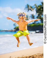 Happy young boy at the beach - Young happy boy having fun on...