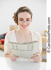 Beautiful young woman wearing glasses for reading newspaper