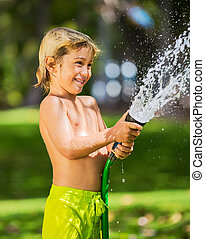 Child, boy or kid plays with water hose outdoors - Happy...