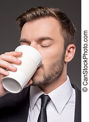 Man drinking coffee. Portrait of confident young men...