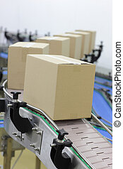 Cardboard boxes on conveyor belt in factory