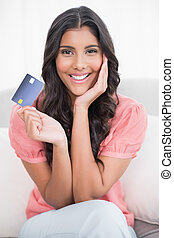 Smiling cute brunette sitting on couch showing credit card...