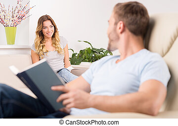Couple at home Cheerful young man reading book and looking...