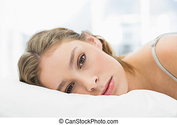 Portrait of tired pretty woman lying in her bed in the...