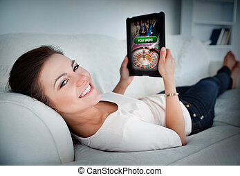 Happy woman lying on couch and gambling on tablet at home in...