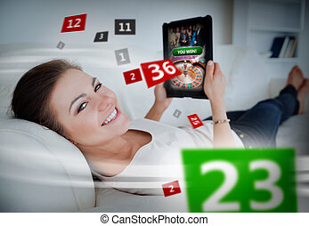 Woman lying on couch and gambling on tablet with holographic...
