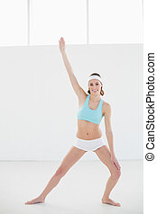 Happy slender woman doing yoga pose standing in sports hall...