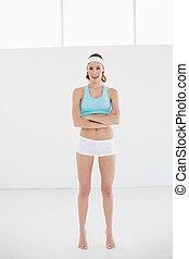 Sporty woman posing in sportswear standing in sports hall...
