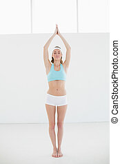Beautiful sporty woman doing yoga pose in sports hall with...