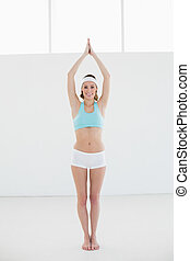 Pretty sporty woman doing yoga pose in sports hall smiling...