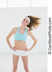Cheerful slender woman posing in sports hall with hands on...