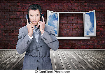 Serious businessman wrapped in cables phoning