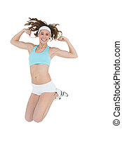 Sporty young woman jumping showing her arm muscles on white...