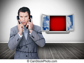 Angry businessman wrapped in cables phoning