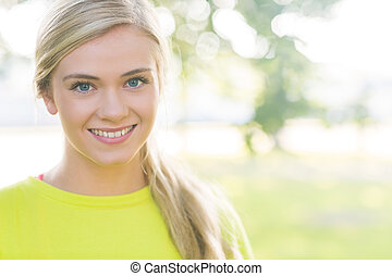 Fit smiling blonde looking at camera in a park on a sunny...