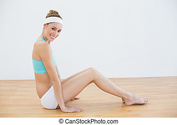 Attractive smiling woman wearing sportswear sitting on floor...