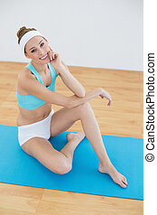Cute woman posing sitting on blue exercise mat in sports...