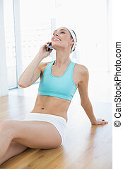 Happy woman in sportswear sitting on floor while phoning...