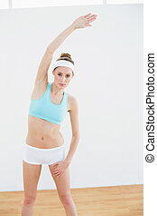 Focused slender woman stretching he body looking at camera...