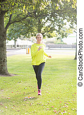 Active smiling blonde jogging towards camera in a park on a...