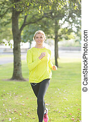 Active happy blonde jogging towards camera in a park on a...
