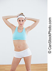 Attractive slim woman posing in sportswear looking at camera...