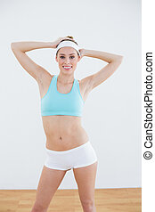 Gleeful young woman in sportswear posing smiling at camera...