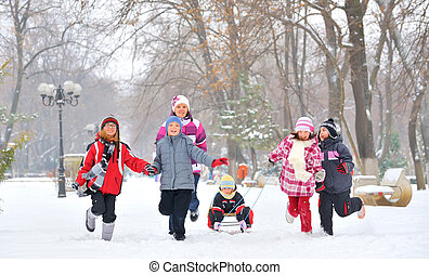 Group of children and mother playing on snow in winter time...