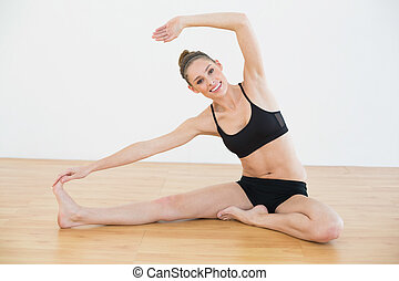 Pretty fit woman stretching her body sitting on the floor in...