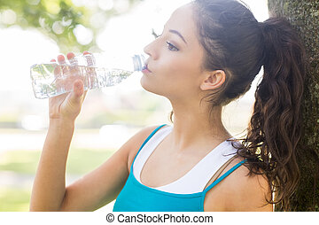 Active calm brunette drinking from a water bottle