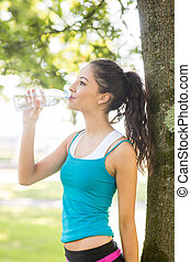Active pretty brunette drinking from a water bottle