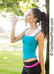 Active attractive brunette drinking from a water bottle