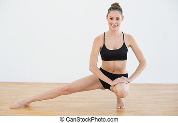 Happy fir woman stretching her leg in sports hall smiling at...