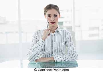 Concentrating chic businesswoman sitting thinking at her...