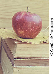 Fresh red apple on old books