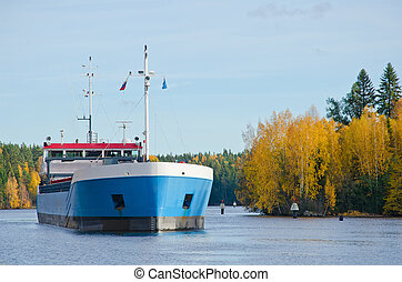 River Cargo Ship - Cargo ship moving down the river autumn...