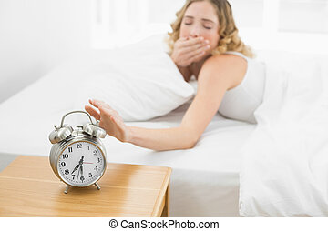 Pretty yawning blonde lying in bed turning off alarm clock