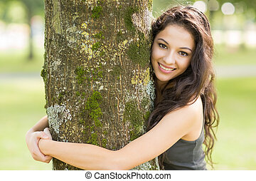 Casual cheerful brunette embracing a tree looking at camera...