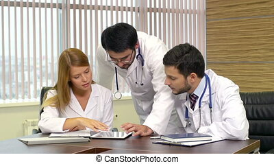 Modern Medicine - General practitioners using a tablet...