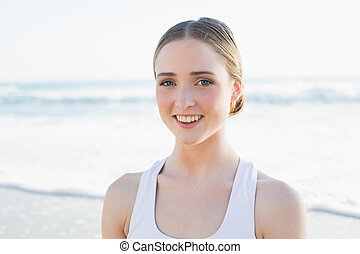 Content young brunette woman sitting on the beach smiling at...
