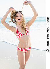 Joyful young woman posing on the beach