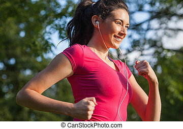 Cheerful young woman jogging in a park while smiling and...