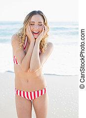 Joyful slender woman posing on the beach