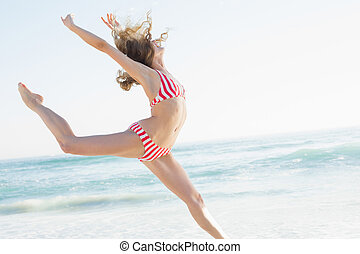 Beautiful young woman jumping on the beach wearing a red...